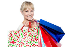 Bolsos de compras que llevan femeninos bonitos sobre hombros Foto de archivo