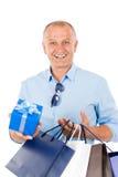 Bolsos de compras smilling maduros del asimiento del hombre Imagen de archivo libre de regalías