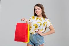 Bolsos de compras sonrientes de la explotación agrícola de la mujer Imagen de archivo libre de regalías