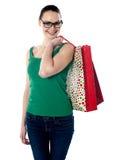 Bolsos de compras sonrientes de la hembra que llevan joven Fotografía de archivo
