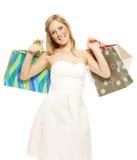 Bolsos de compras sonrientes de la mujer que llevan joven fotografía de archivo libre de regalías