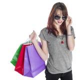 Bolsos de compras sonrientes de la mujer que llevan joven Fotos de archivo libres de regalías