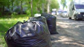 Bolsos de la basura por el camino almacen de video