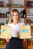 Bolsos de ofrecimiento de la mujer en comida sana Imágenes de archivo libres de regalías