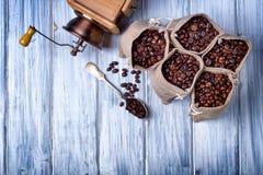Bolsos del yute con los granos y la amoladora de café Fotografía de archivo