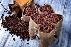Bolsos del yute con los granos y la amoladora de café Foto de archivo
