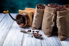 Bolsos del yute con los granos y la amoladora de café Imágenes de archivo libres de regalías