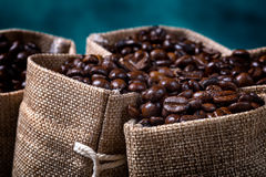 Bolsos del yute llenados de los granos de café Fotos de archivo libres de regalías
