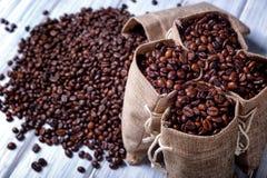 Bolsos del yute llenados de los granos de café Imágenes de archivo libres de regalías
