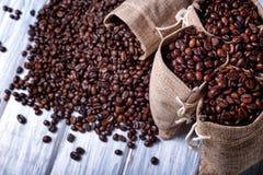 Bolsos del yute llenados de los granos de café Foto de archivo