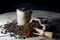 Bolsos del yute llenados del café molido y de los granos de café en una tabla de madera rústica vieja en negro Foto de archivo libre de regalías