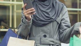 Bolsos que llevan de la mujer musulmán feliz con las compras, llamando el taxi después de hacer compras metrajes