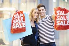 Bolsos que llevan de los pares felices en alameda de compras Foto de archivo libre de regalías