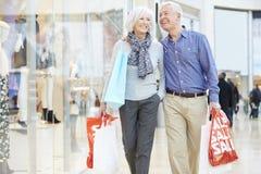 Bolsos que llevan de los pares mayores felices en alameda de compras Imágenes de archivo libres de regalías