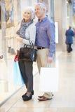 Bolsos que llevan de los pares mayores felices en alameda de compras Imagenes de archivo
