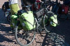 Bolsos verdes de la bicicleta para los viajes largos en el fondo de las piedras de pavimentación fotografía de archivo libre de regalías