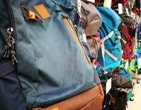 Bolsos y mochilas en diversos tipos y colores en tienda foto de archivo