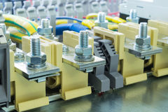 Bolt bushing terminals on the DIN rail located on the mounting panel Royalty Free Stock Image