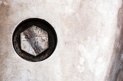 Bolt head in grunge metal. A scratched and worn bolt head sunk into an industrial metal panel Royalty Free Stock Photos