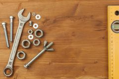 Bolt and nut on a wooden background. Mounting spanner. Background with working tools. Workshop equipment. Royalty Free Stock Photo