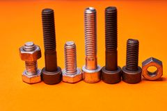 Bolted connecting elements on orange background close-up.  royalty free stock photos