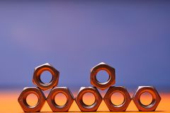 Bolted connecting elements on orange, blue background close-up.  royalty free stock photography