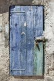 Bolted and locked rugged wooden door painted blue. Concrete wall with layers of uneven plaster and old wooden door, painted blue, bolted and locked Stock Photo