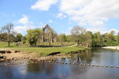 Bolton Abbey Priory. The ruins of Bolton Abbey Augustinian Priory near Skipton, Yorkshire, UK. The iconic stepping stones cross the river Wharfe. A popular UK Stock Image