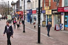 Bolton, UK. APRIL 23: People walk along a shopping street on April 23, 2013 in . Bolton is part of Greater Manchester, one of largest population areas in the Royalty Free Stock Images