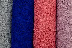 Bolts of lace fabric blue, pink, magenta and gray colors. Colorful swatches of lace fabric on shopfront. A lot of fabric rolls. Bolts of lace fabric blue, pink Stock Images