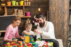 bolts muttrar för sammansättningsbegreppsfamilj Familjlek med färgrika tegelstenar Familjbyggandestruktur med leksaktegelstenar F Royaltyfri Bild