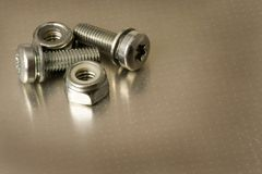 Bolts and nuts on metal. Closeup of bolts and nuts on a metal surface stock images