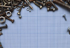 Bolts and nuts on the millimeter paper. Free space. Free space frame of millimeter paper and bolts. A lot of scrap and metal Royalty Free Stock Photos