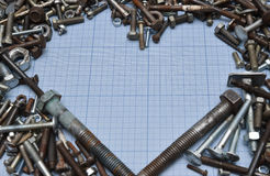 Bolts and nuts on the millimeter paper. Heart shaped. Free space. Free space frame of millimeter paper and bolts. A lot of scrap and metal. Heart shaped Royalty Free Stock Photo