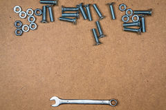 Bolts nuts and spanner on the bottom Royalty Free Stock Photos