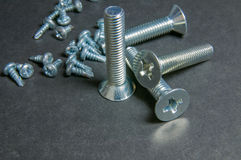 Bolts and Screws on grey. Centre upright bolt Stock Photos