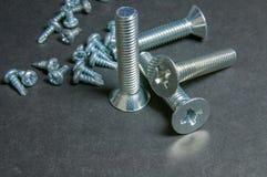 Bolts and Screws on grey. Centre upright bolt. Silvery four bolts and pile screws on grey. Centre upright bolt Stock Photos