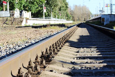 bolts that secure the rails to the sleepers on the railway direction. Royalty Free Stock Photo