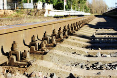 bolts that secure the rails to the sleepers on the railway direction. Royalty Free Stock Image