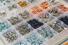 Bolzen, Schrauben, Nüsse, Niete auf einem Zähler des Shops Stockfotos