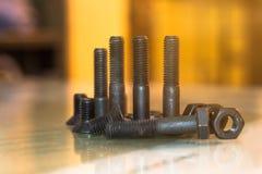 Bolzen und Nüsse auf Glastisch in der Industrie bereiten sich für Reparatur wor vor Lizenzfreie Stockfotos