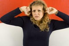 Bolzenfinger der jungen Frau in seinen Ohren Stockbild