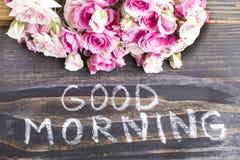 Bom dia das palavras com rosas cor-de-rosa em um fundo de madeira rústico Imagem de Stock Royalty Free