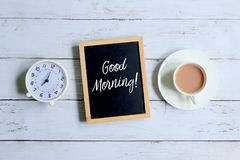 Bom dia escrito em um quadro-negro com pulso de disparo e café Fotografia de Stock