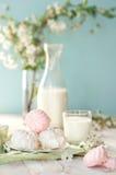 Bom dia! Marshmallow ou zéfiro do russo com garrafa e vidro do leite no fundo da árvore Composição da mola Fotos de Stock