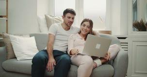 Bom dia para o sorriso de uns pares e o assento feliz no sofá e que olham algo engraçado, estilo acolhedor agradável na vida filme