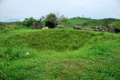 Bomb craters from the Vietnam War surround giant megalithic stone urns at the Plain of Jars archaeological site in Loas. This area is the world`s most heavily Royalty Free Stock Photo