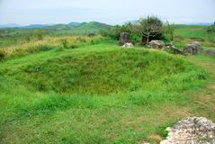 Bomb craters from the Vietnam War surround giant megalithic stone urns at the Plain of Jars archaeological site in Loas. This area is the world`s most heavily Stock Photos