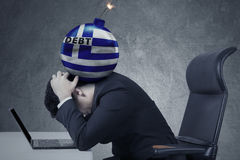 Bomb of debt with a Greece flag on the man head Stock Photography