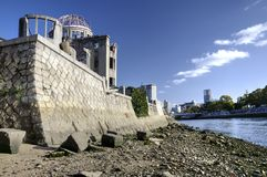 A-Bomb Dome and river bank in Hiroshima, Japan. Atomic Bomb Dome, wall and Motoyasu river  in Hiroshima, Japan. This serves as an important landmark marking the Stock Photos